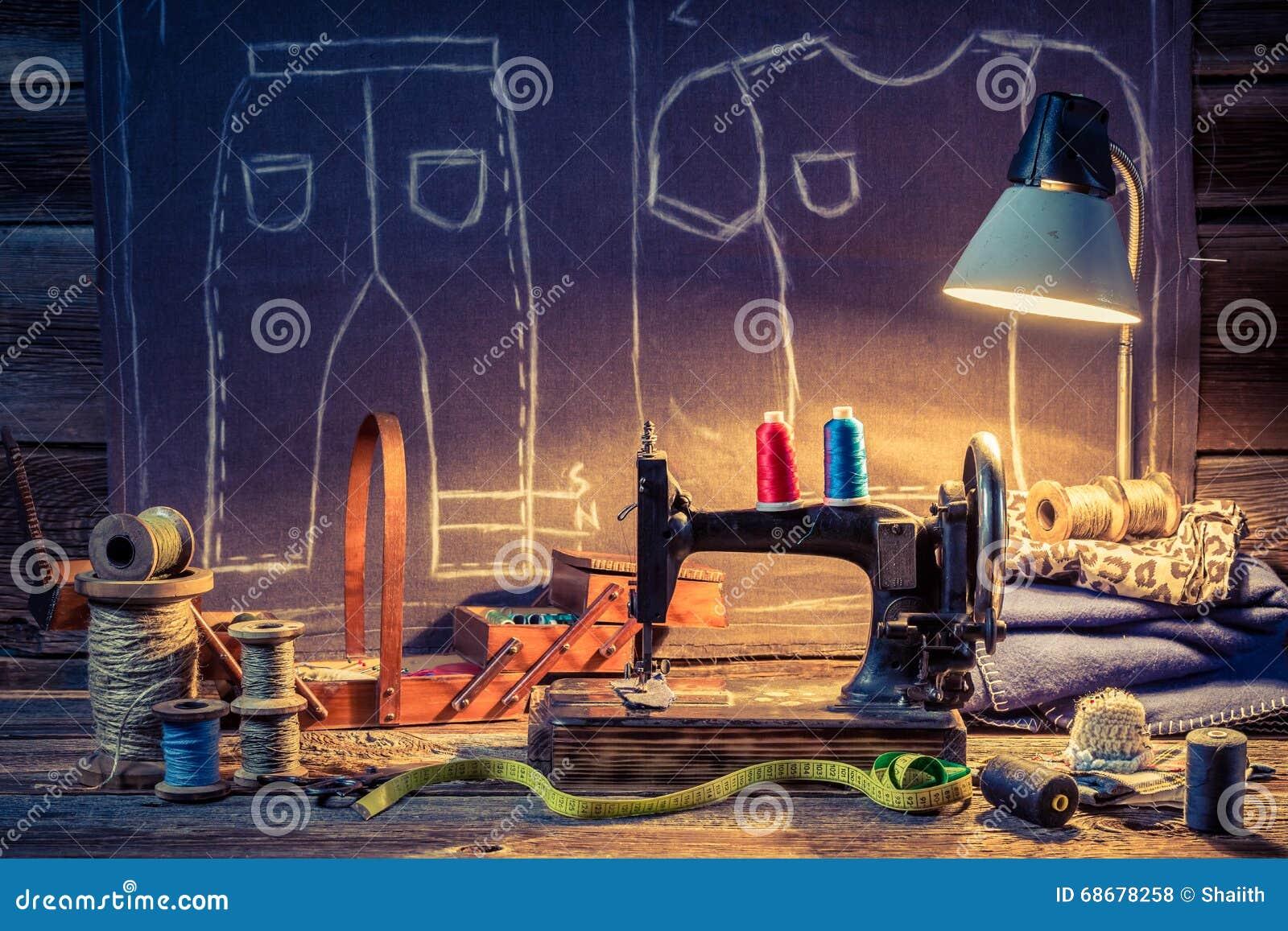 Oficina velha do alfaiate com máquina de costura e pano