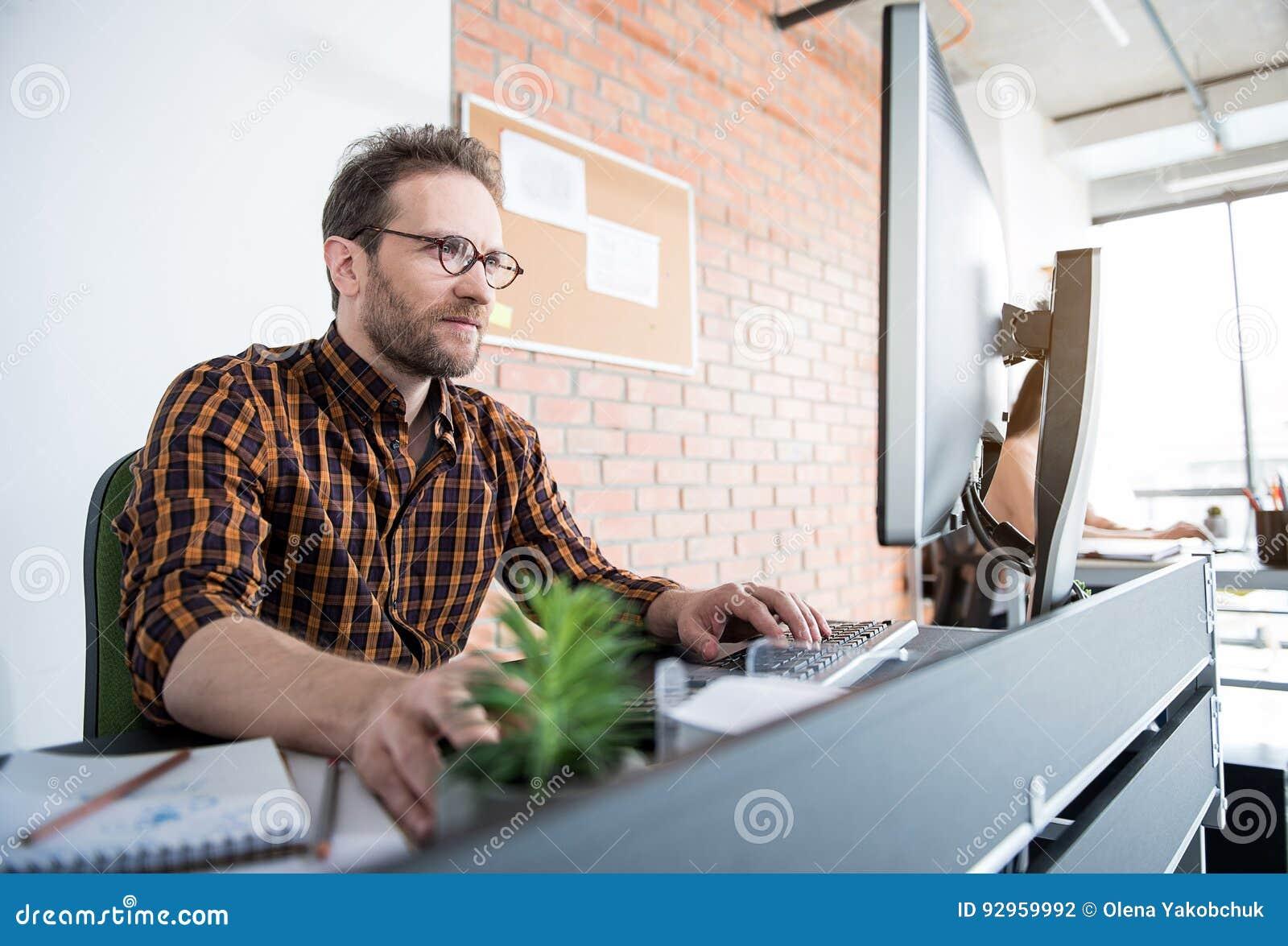 3c1139a0f0e5e El encargado ocupado serio está trabajando en el ordenador Él que se sienta  en el lugar de trabajo en oficina Ángulo inferior