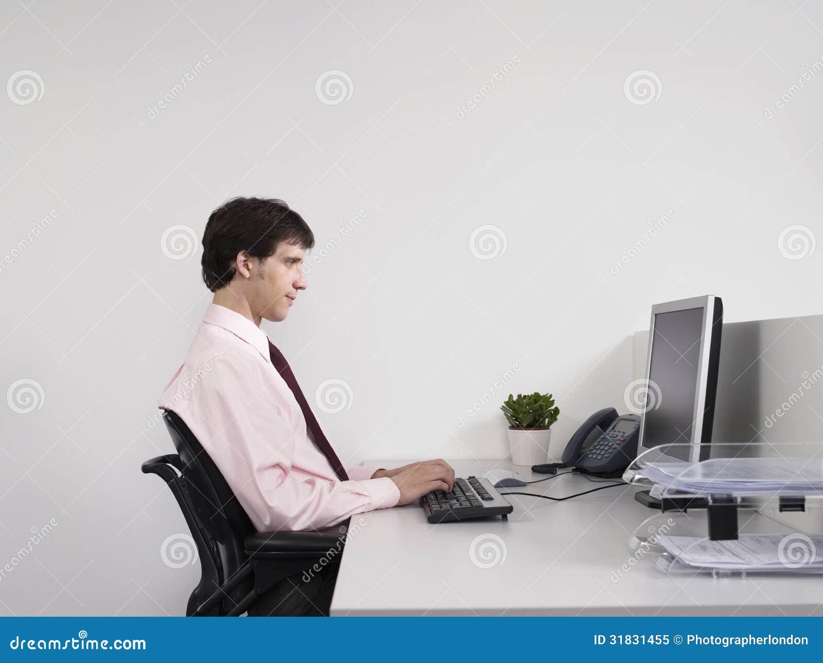 Oficinista de sexo masculino que usa el ordenador en el for Que es un oficinista