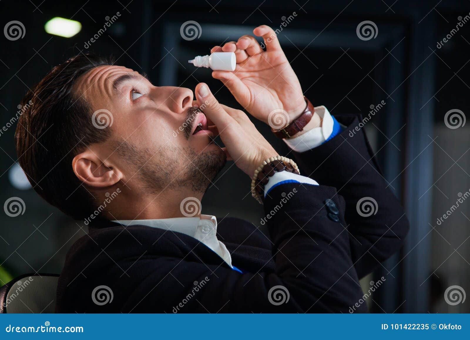 Oficinista que sufre el síndrome del ojo seco, descensos de ojo de los rasgones artificiales