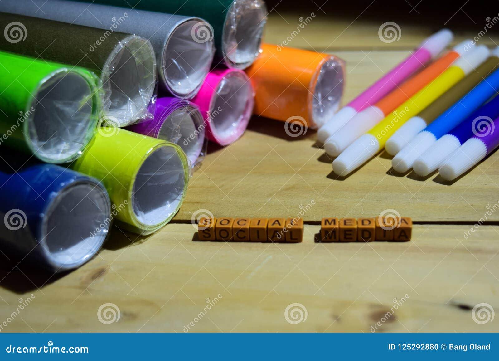 Ogólnospołeczni środki na drewnianych sześcianach z kolorowym papierem i piórem, pojęcie inspiracja na drewnianym tle