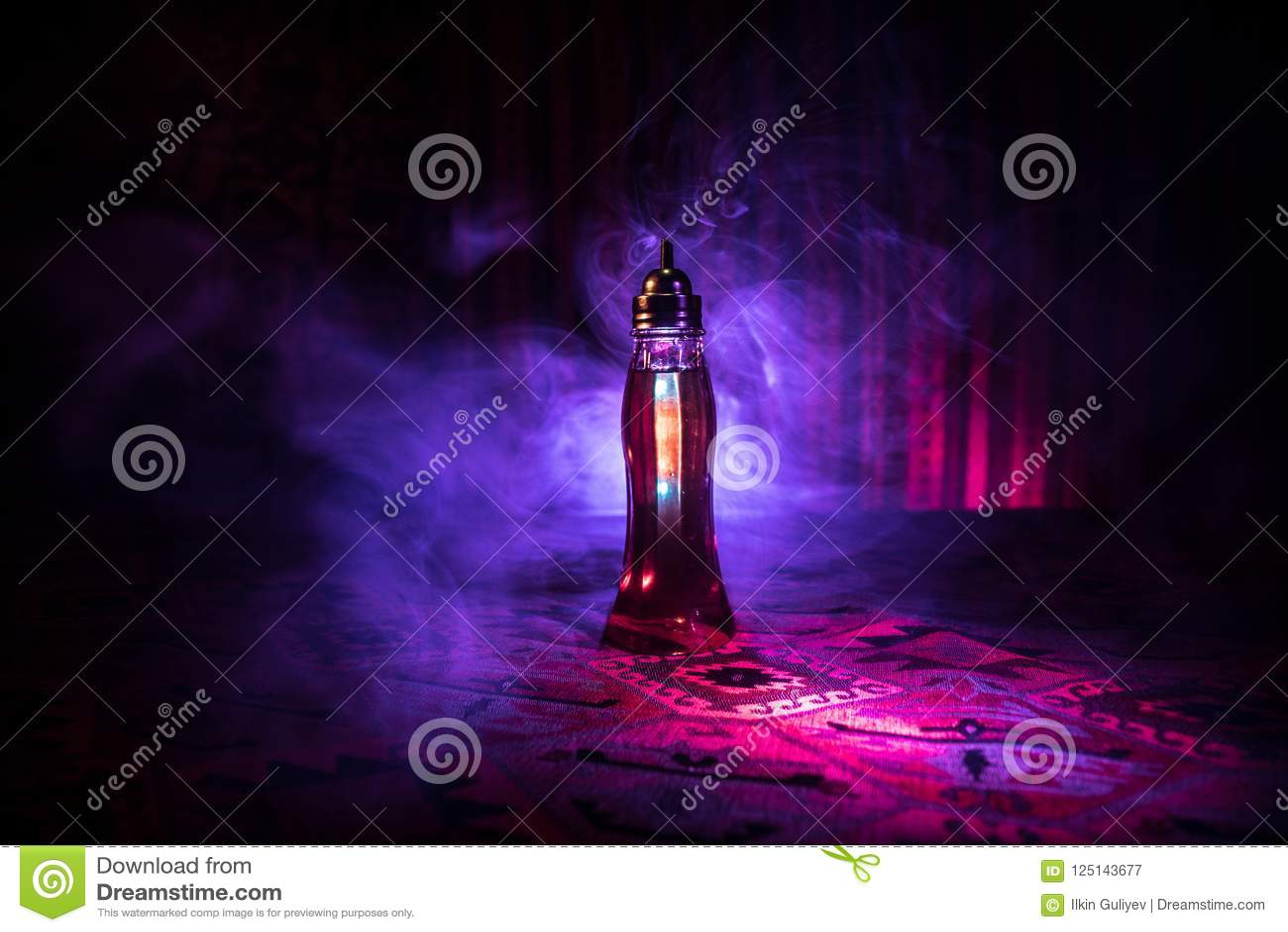 Oggetto d antiquariato e bottiglie di vetro d annata su fondo nebbioso scuro con luce Veleno o concetto del liquido di magia