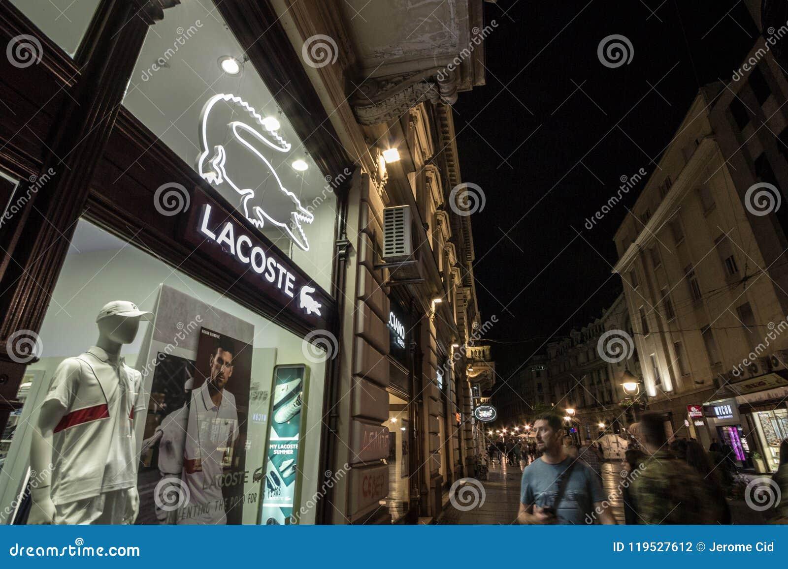 c0c411fbec63 Photo du signe de Lacoste sur leur boutique à Belgrade, Serbie, le soir,  avec des personnes passant par dans la rue Lacoste est une entreprise de  mode, ...
