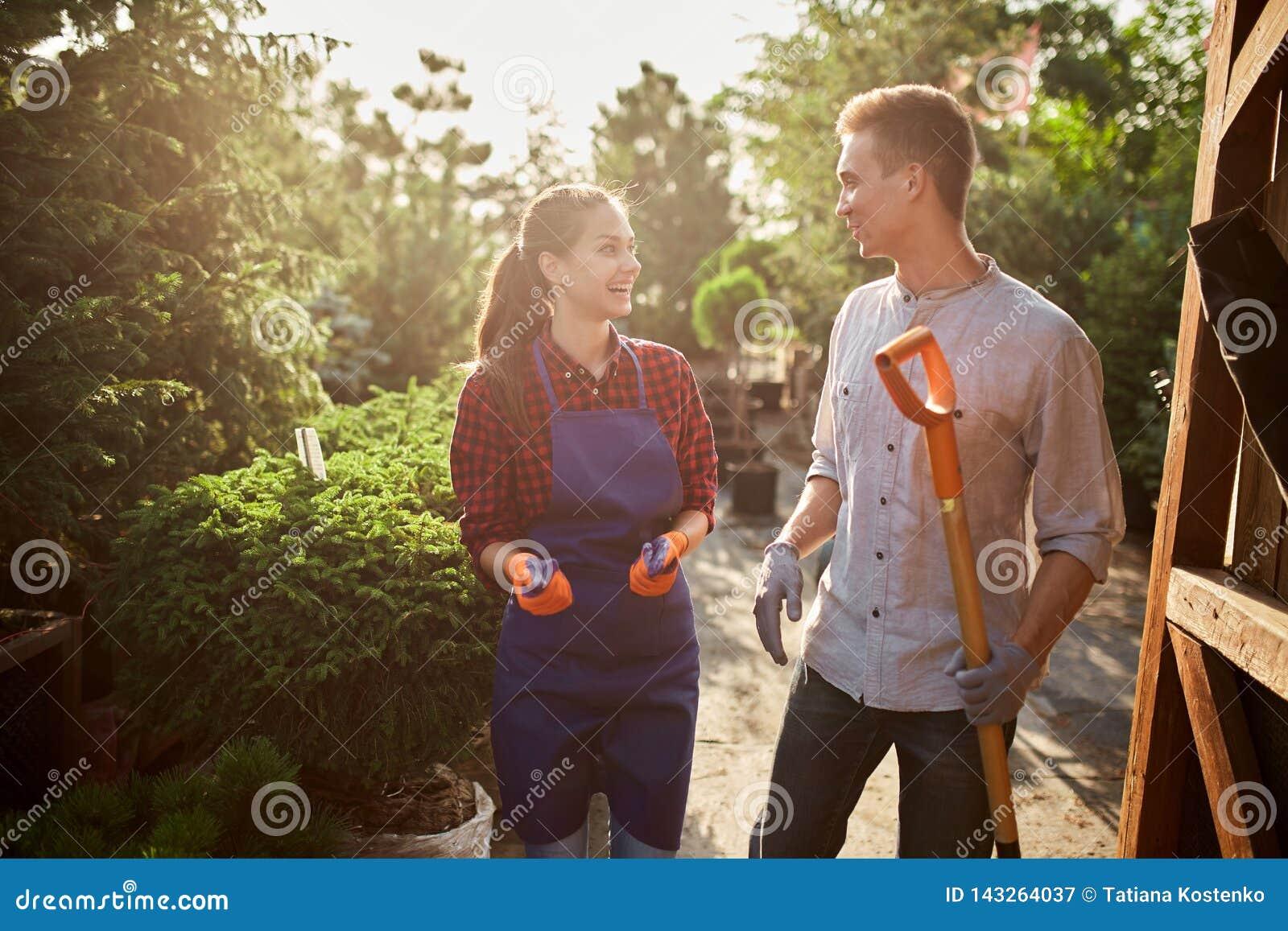 Ogrodniczki ładna dziewczyna w facecie z łopaty odprowadzeniem na ogrodowej ścieżce w cudownym ogródzie na słonecznym dniu i fart