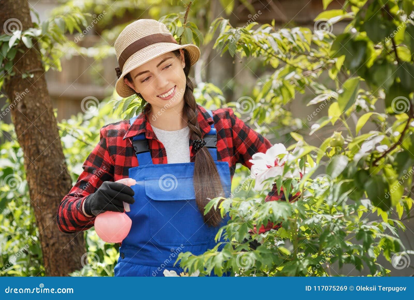 Ogrodniczki opryskiwania woda na kwiatach lub pestycyd