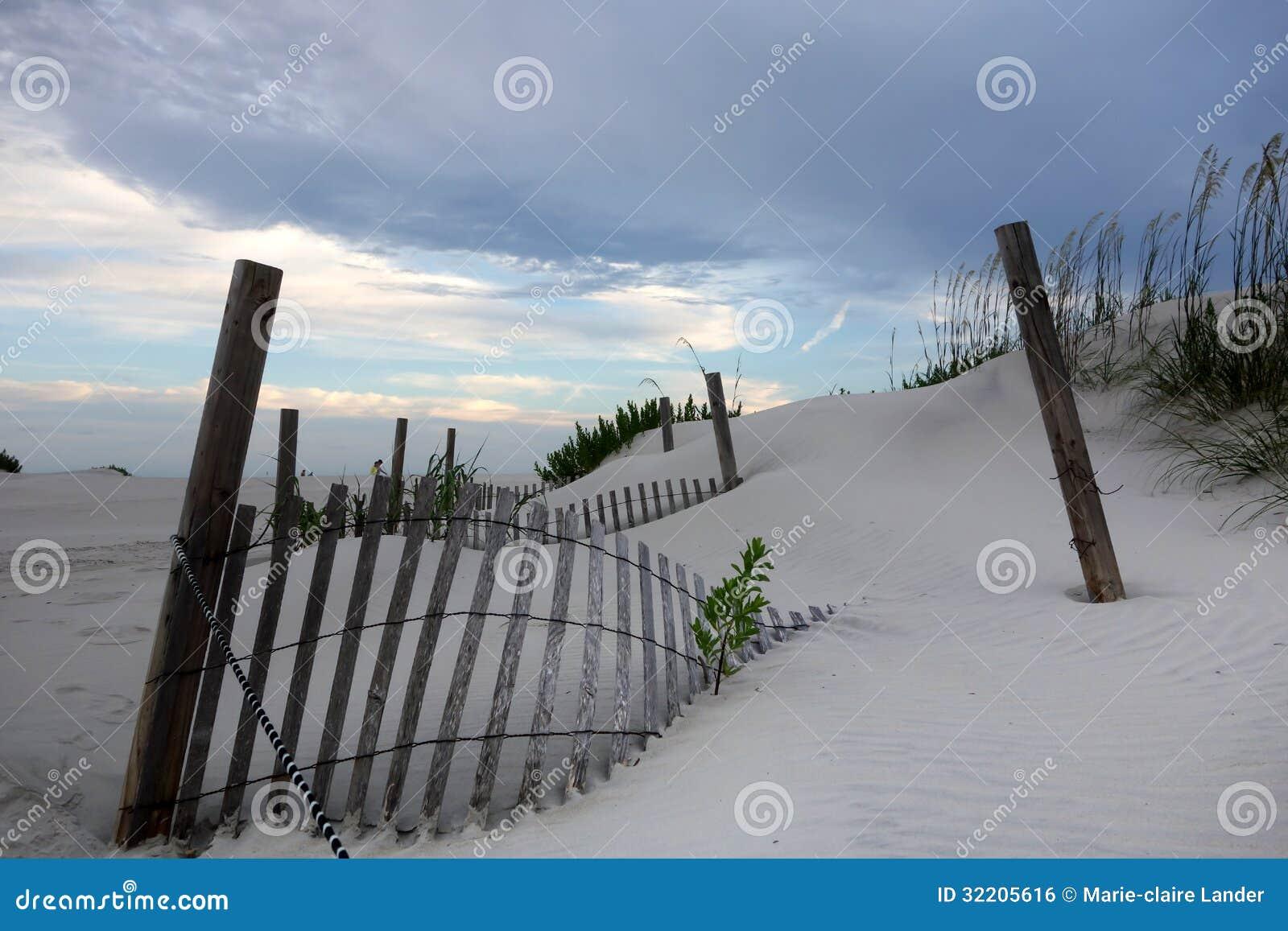 Ogrodzenie zakopujący w piasek diunach i ładnych niebach