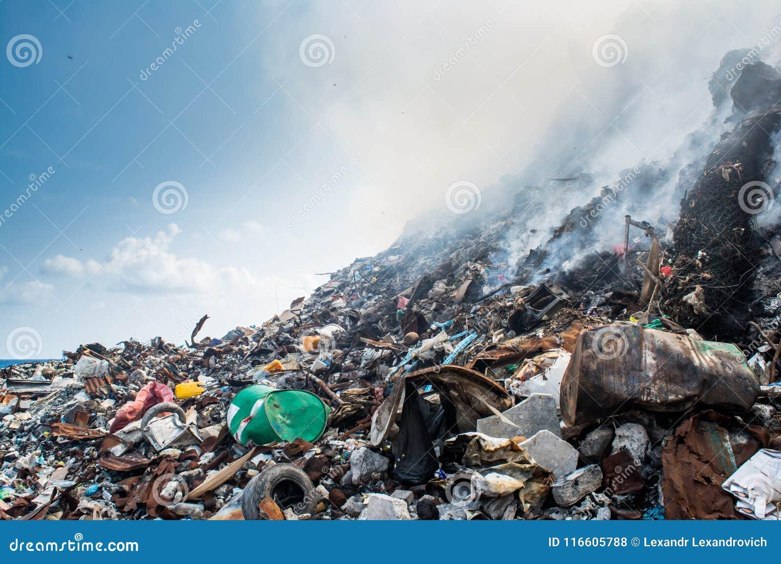 Ogromny śmieciarskiego usypu terenu widok pełno dym, ściółka, klingeryt butelki, banialuki i inny grat przy Thilafushi wyspą,