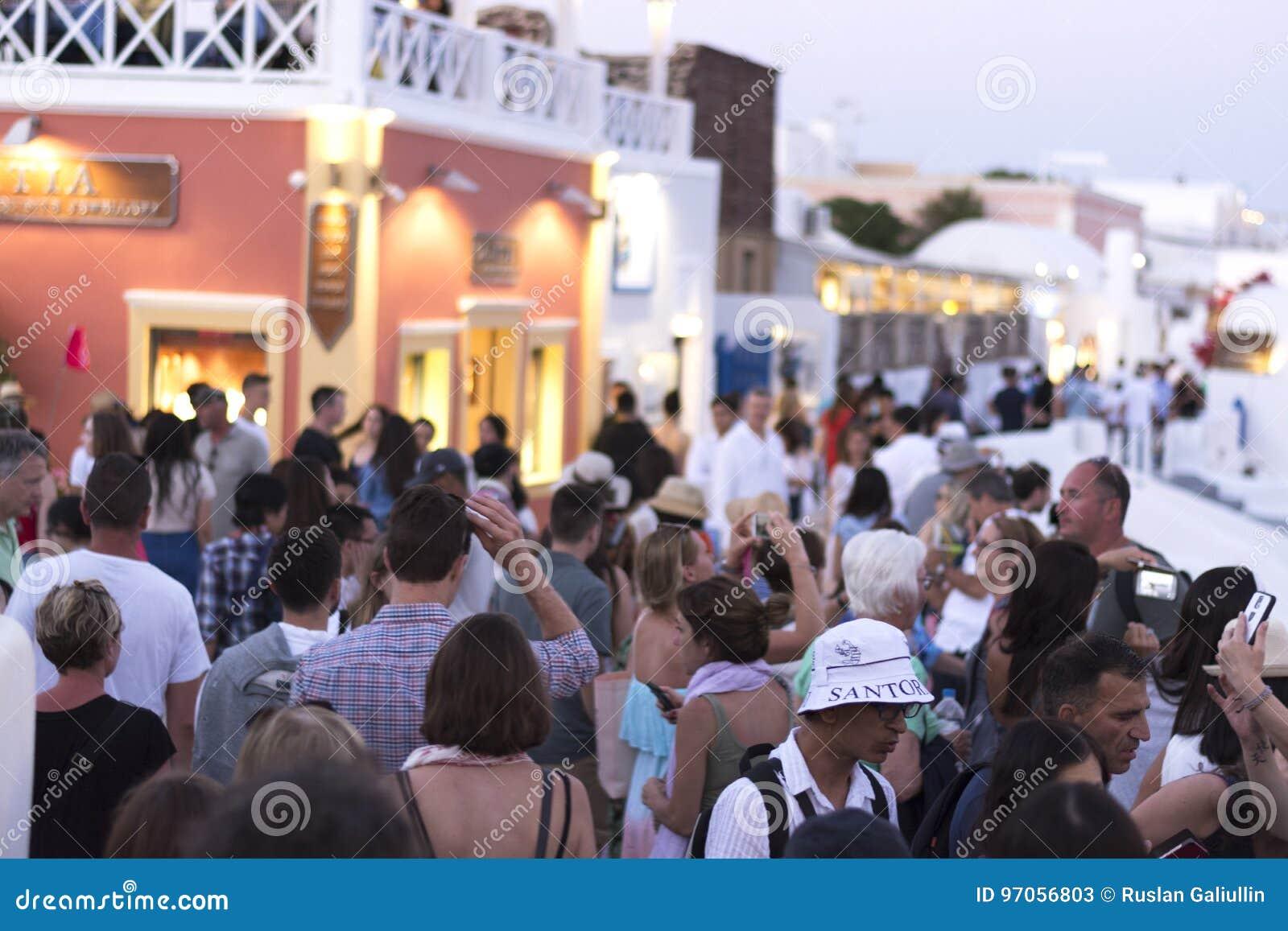 Oia Santorini, GREKLAND - Juni 9, 2017: EN FOLKMASSA AV TURISTER VÄNTAR PÅ DEN BERÖMDA SANTORINI-SOLNEDGÅNGEN