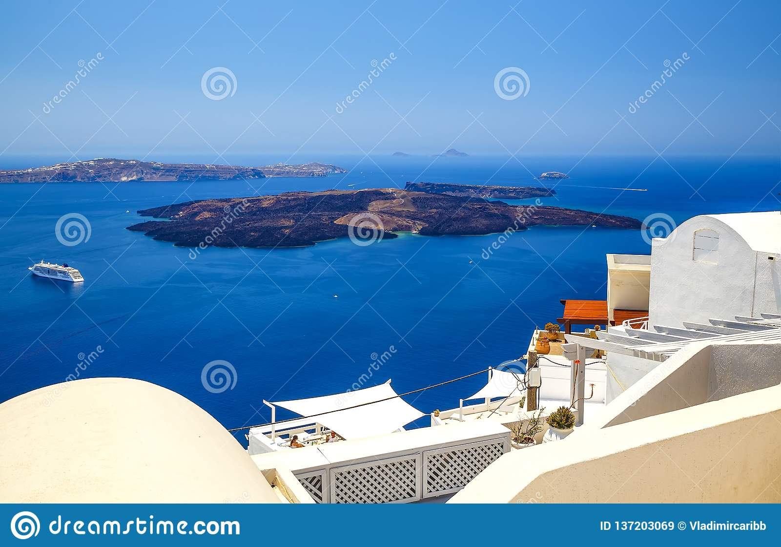 Oia town on Santorini island, Greece. Traditional and famous houses and churches with blue domes over Caldera, Aegean sea color