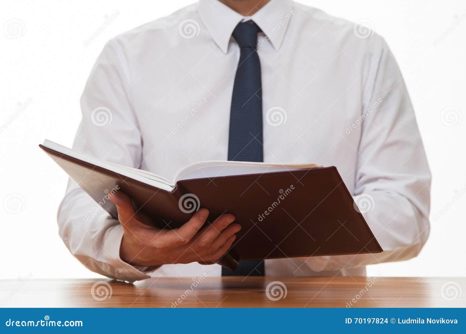 Oigenkännlig affärsman som läser en bok