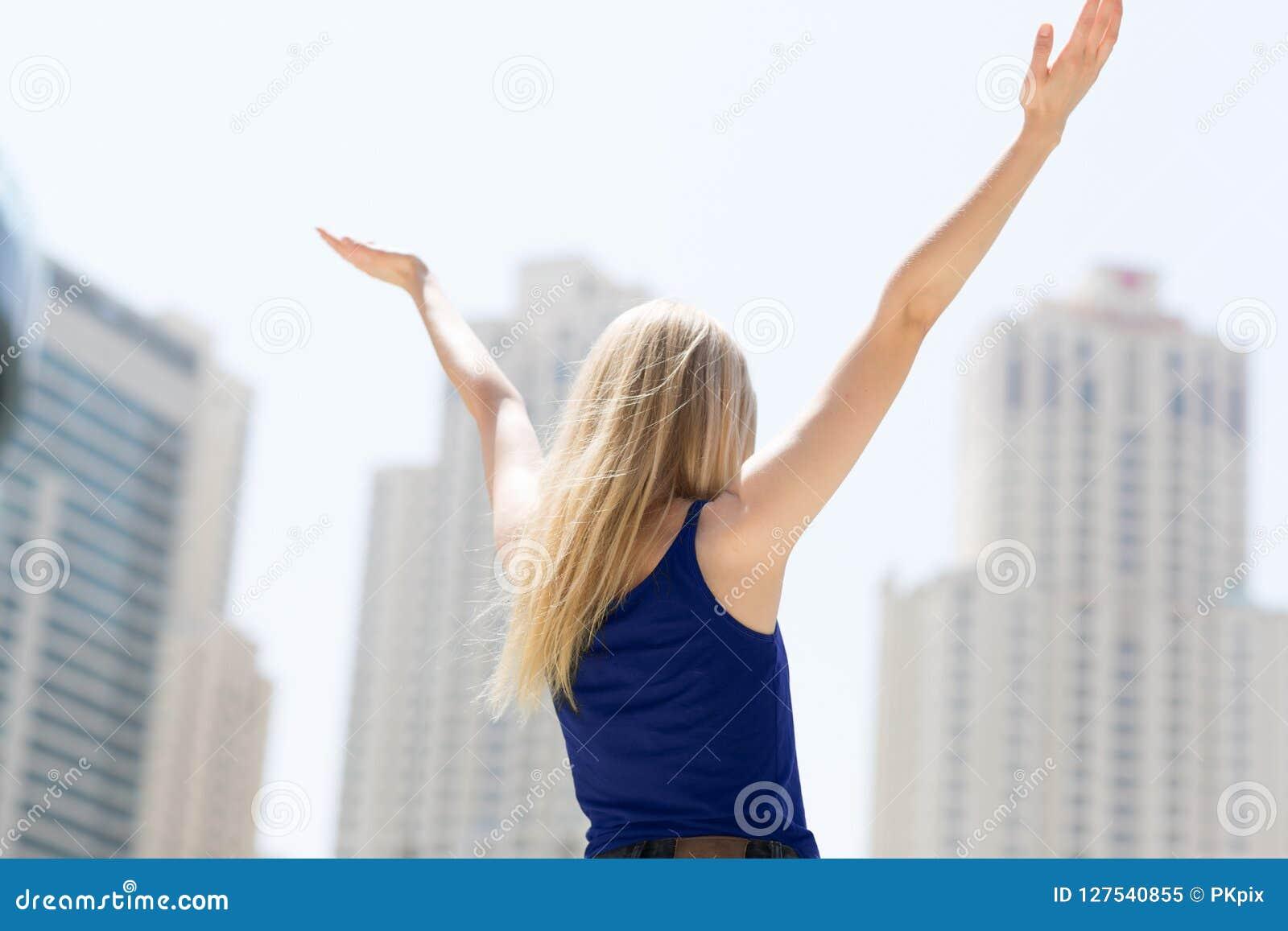 Oigenkännlig kvinna som förbiser staden med hennes armar upp i luften isolerad white för beröm begrepp