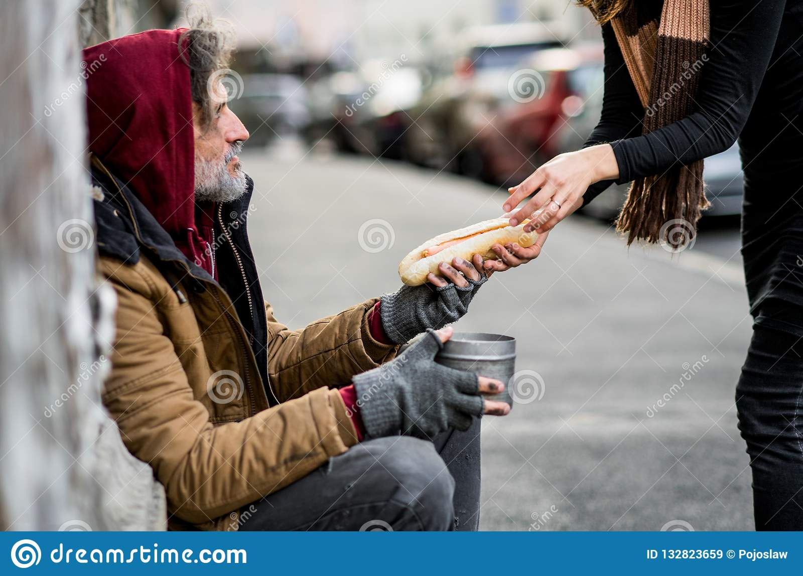 Oigenkännlig kvinna som ger mat till den hemlösa tiggaremannen som sitter i stad