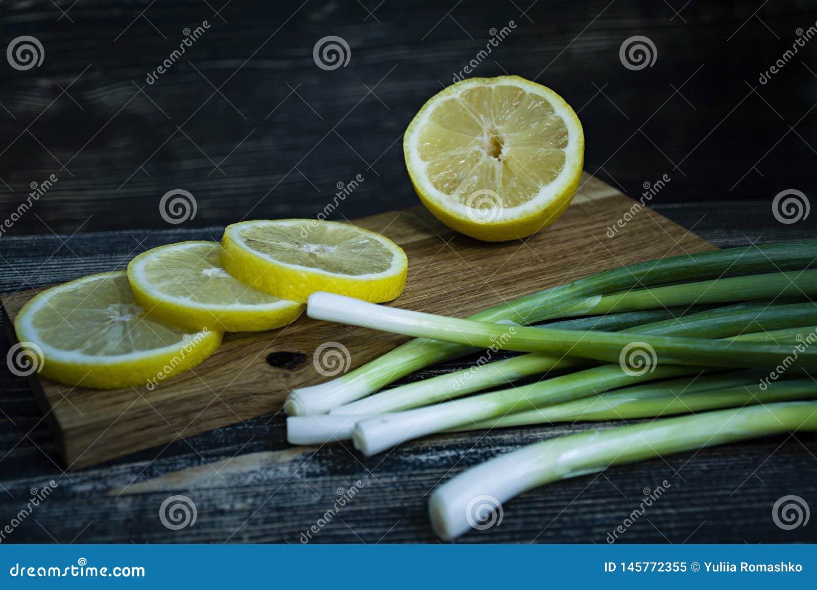 Oignons de ressort et citron de découpage en tranches sur un fond en bois foncé