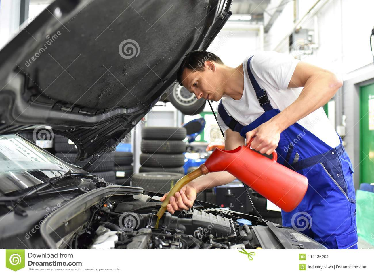 oil change from the engine of a car in a workshop by a professional mechanic - after-sales service