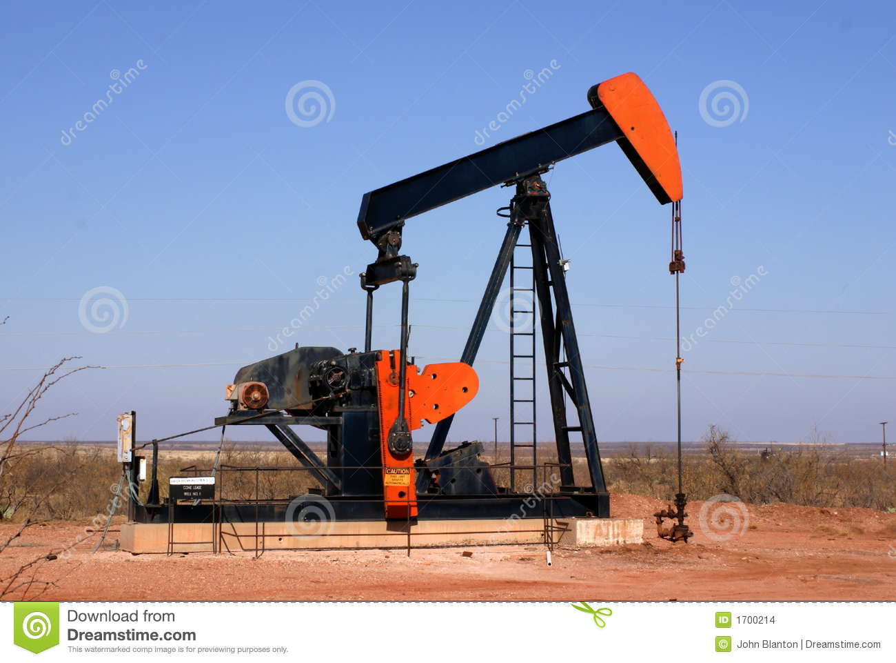 Oil well pump showing walking beam horse head and polished rod.