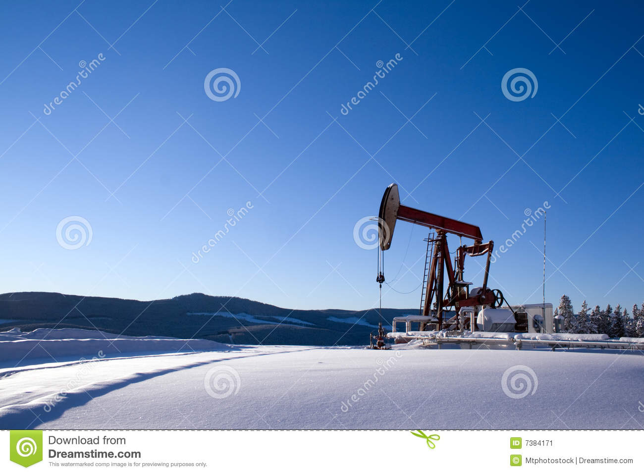 Oil well pumpjack mountain snow