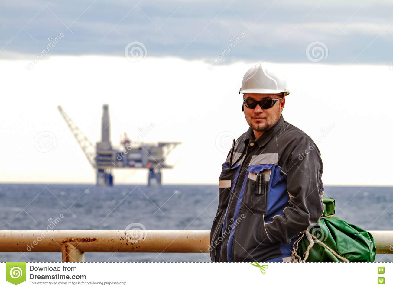 Oilman shift workers on the deck of the ship on the background offshore oil shelf planforms. Work on the way to work