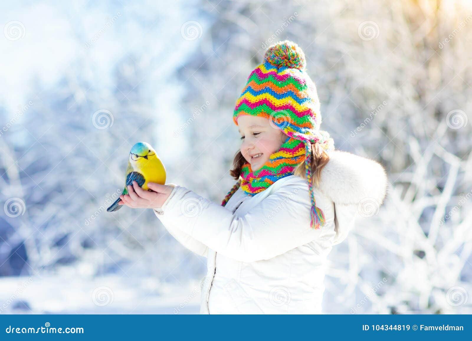 Oiseau d alimentation des enfants en parc d hiver Jeu d enfants dans la neige nature et