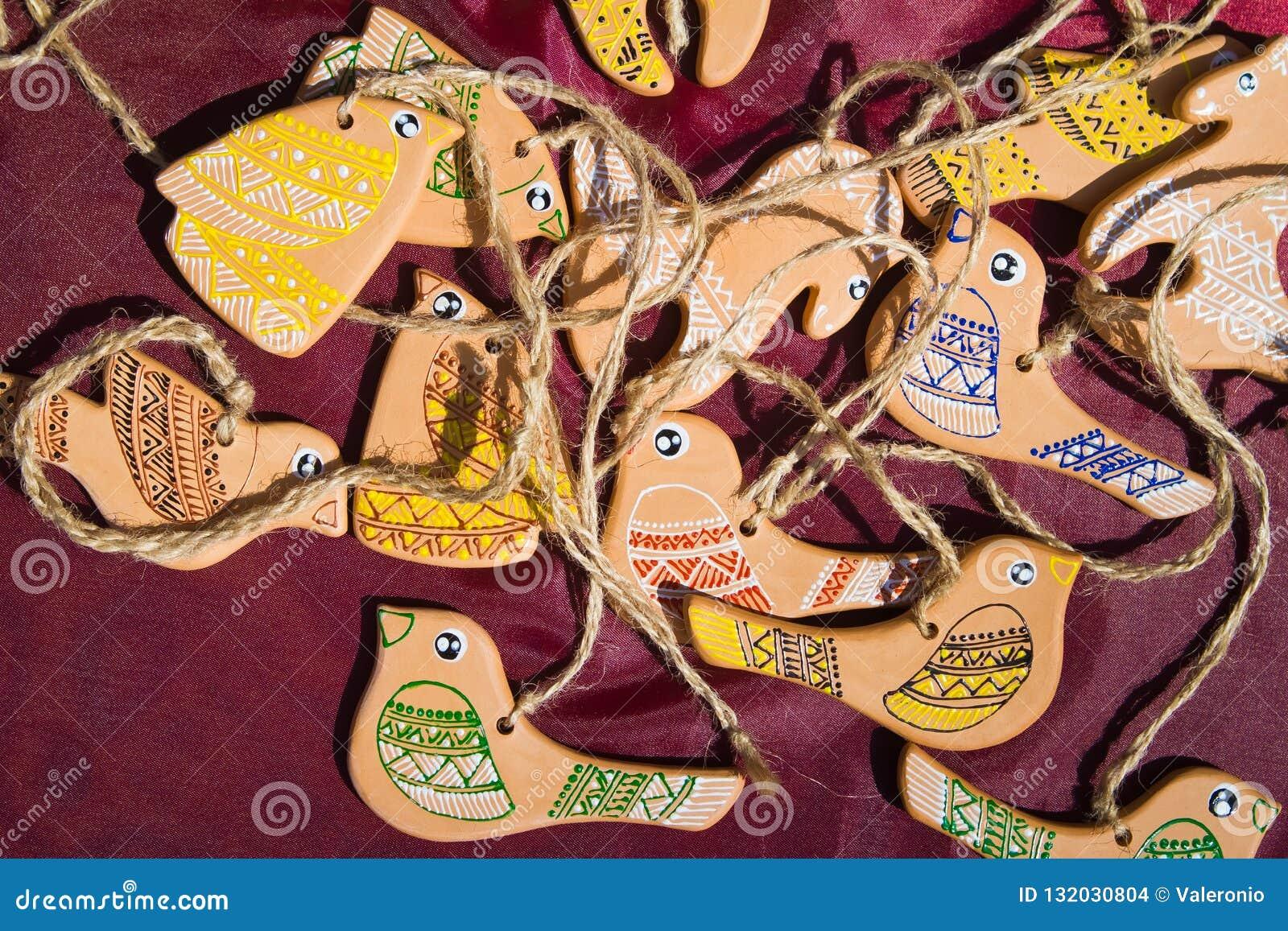 Oiseaux et chevaux de jouet faits main de l argile et peints à la main avec des fils à accrocher