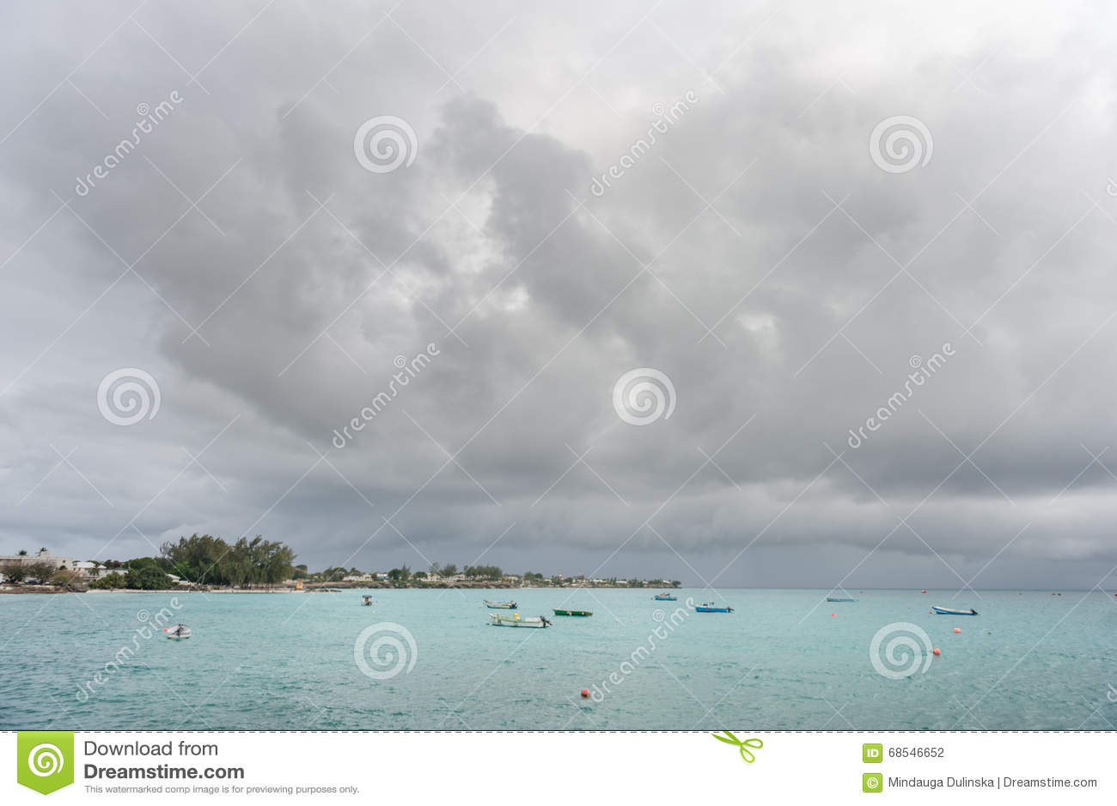 OISTINS, BARBADOS - 15. MÄRZ 2014: Miami Beach in Barbados mit bewölktem stürmischem Himmel und Yacht, Boote im Hintergrund