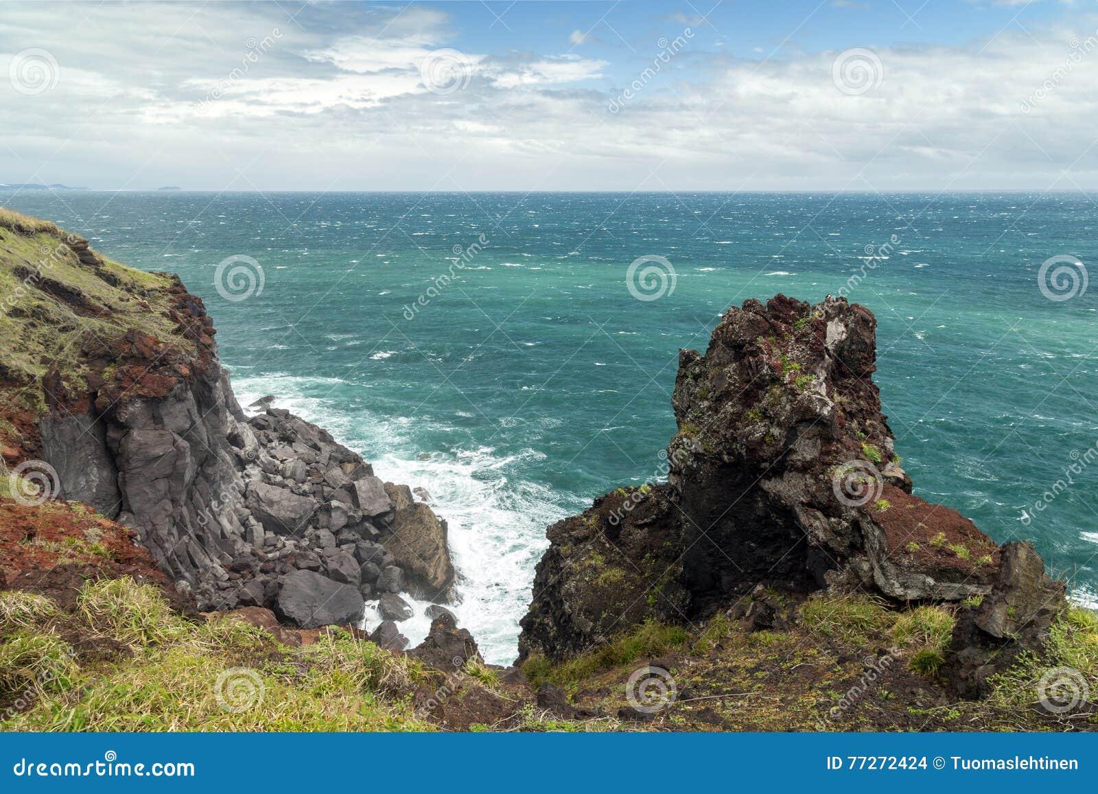 Ojämn brant klippa, brant klippa och hav på den Jeju ön