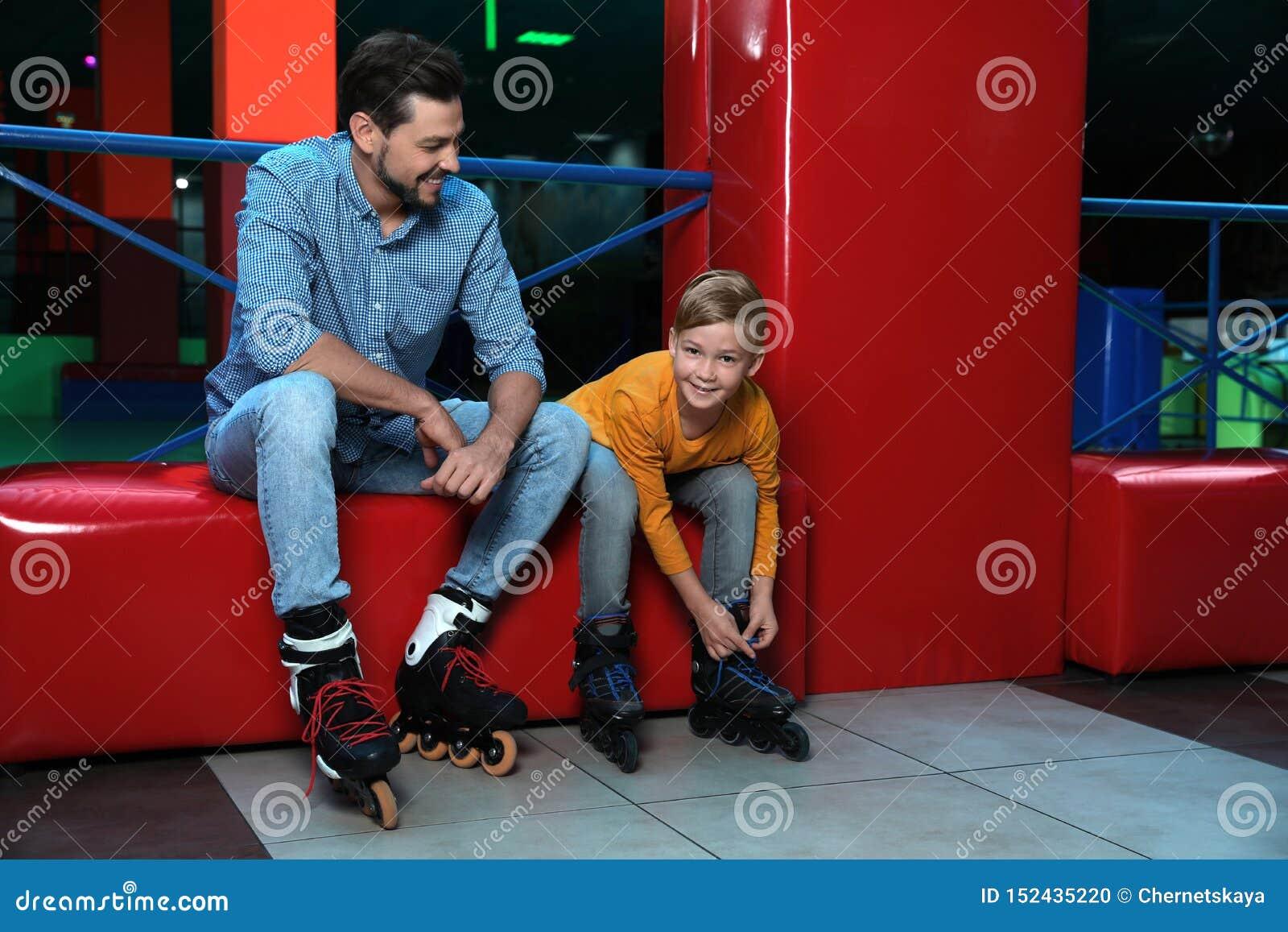 Ojca i syna kładzenie na rolkowych łyżwach