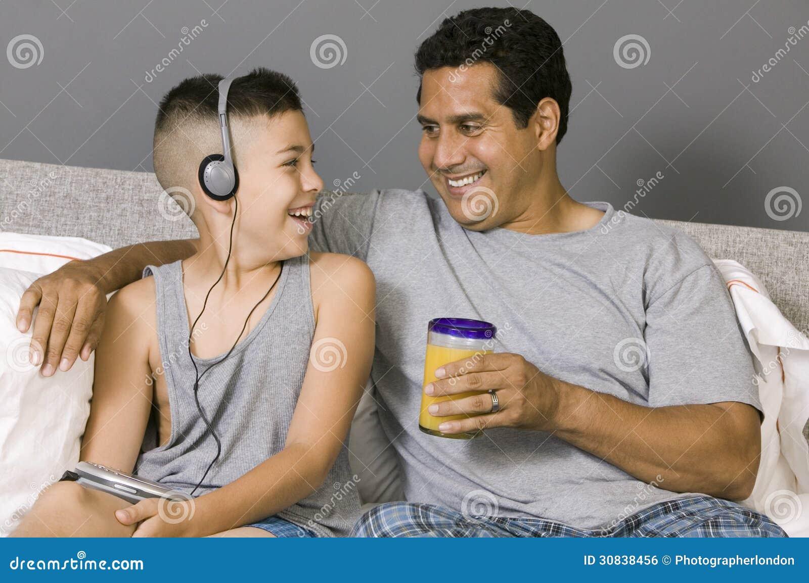 Ojca i syna obsiadanie na łóżkowym słuchaniu muzyka