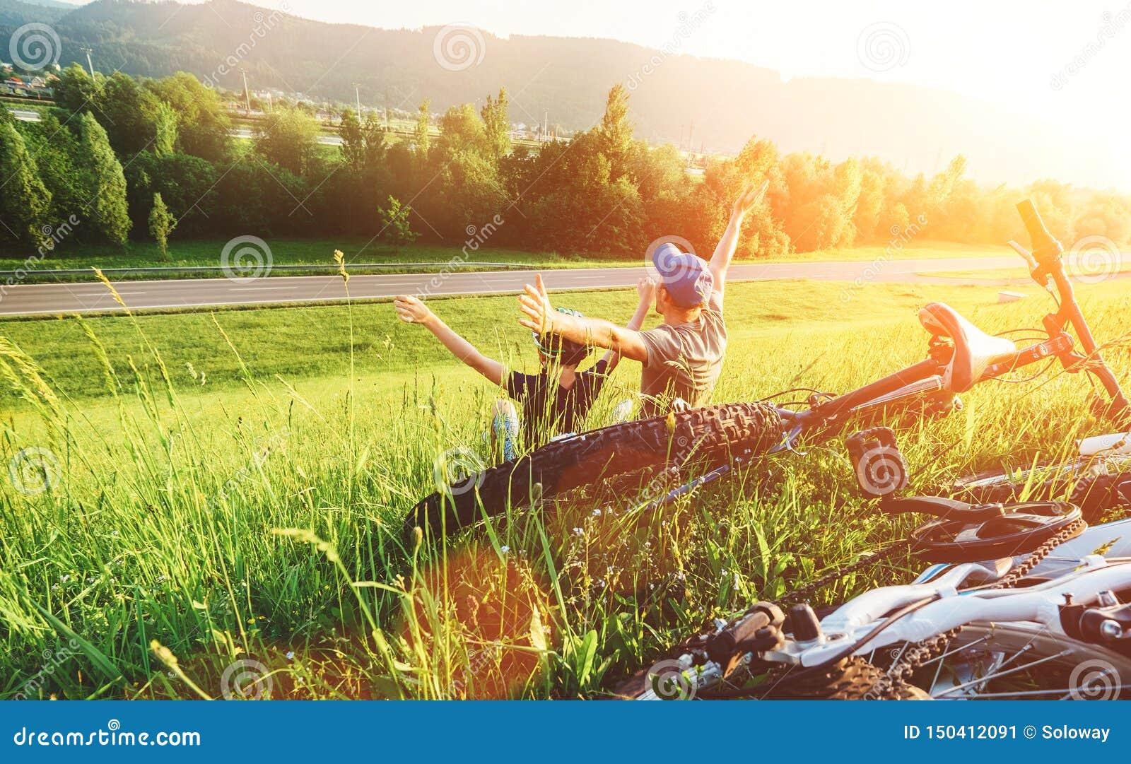 Ojca i syna odpoczynek wp?lnie w zielonej trawie gdy rowerowego spacer
