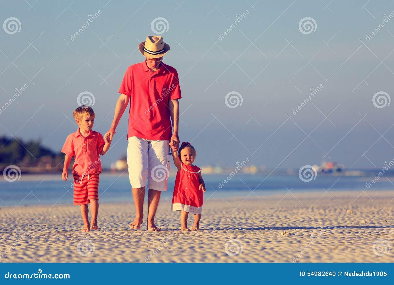 Ojciec i dwa dzieciaka chodzi na lecie wyrzucać na brzeg
