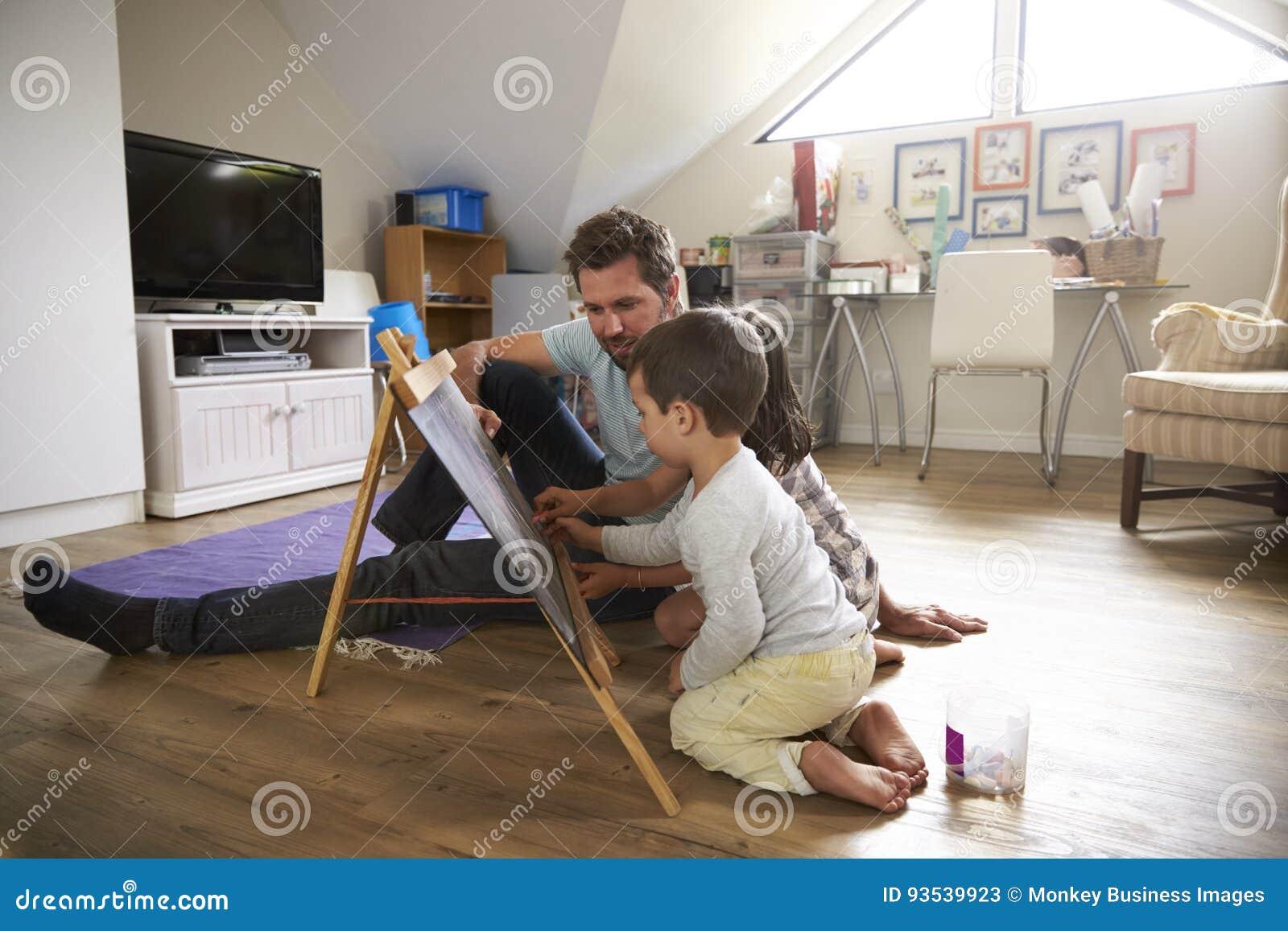 Ojciec I dzieci Rysuje Na Chalkboard W Playroom