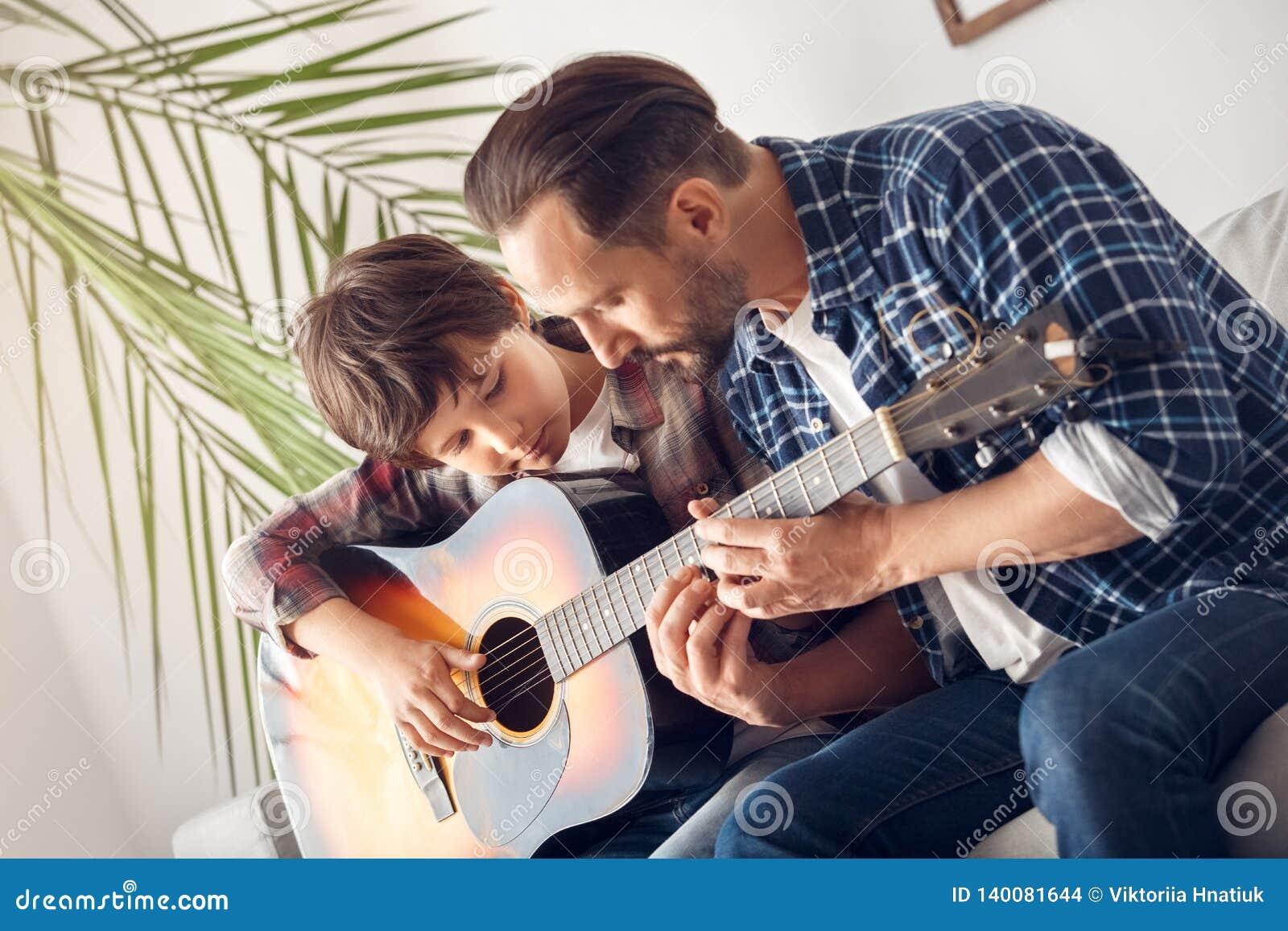Ojciec i mały syn siedzi na kanapy chłopiec z gitara tatą pokazuje akordy rozważnych w domu