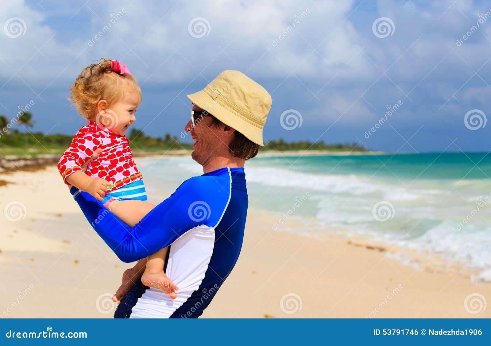Ojciec i mała córka ma zabawę na plaży