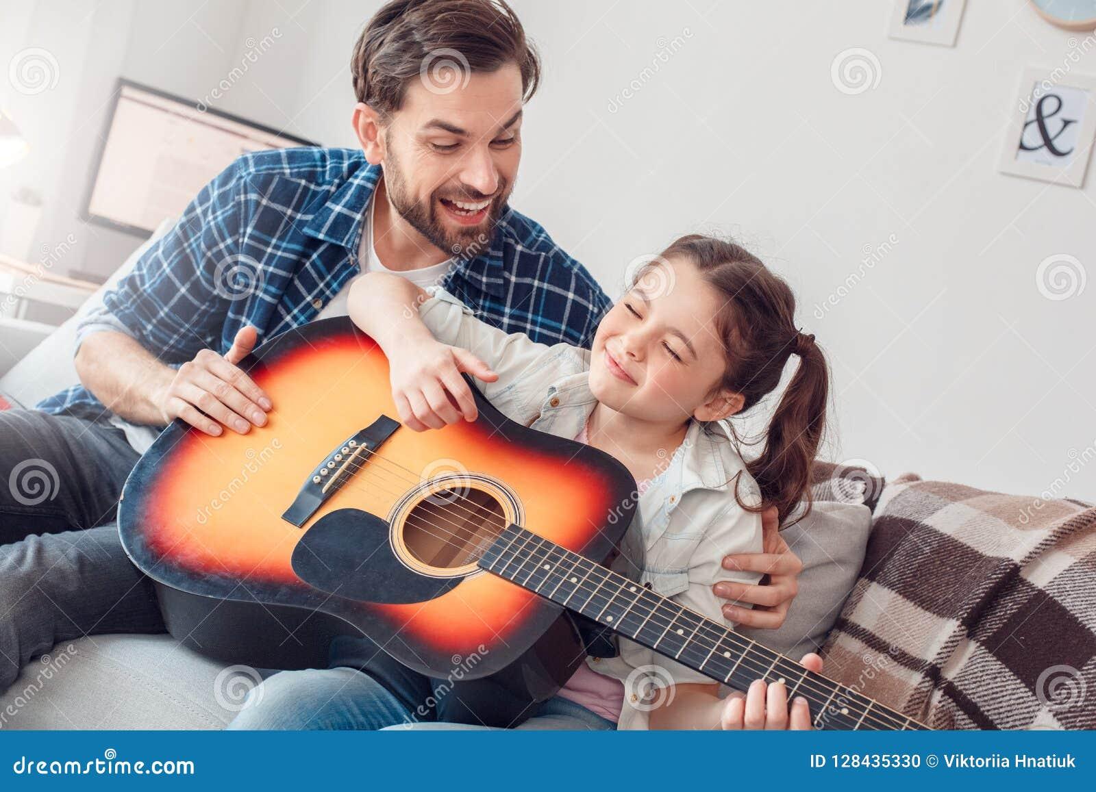 Ojciec i mała córka siedzi mężczyzna przytulenia córki bawić się gitarę radosną w domu
