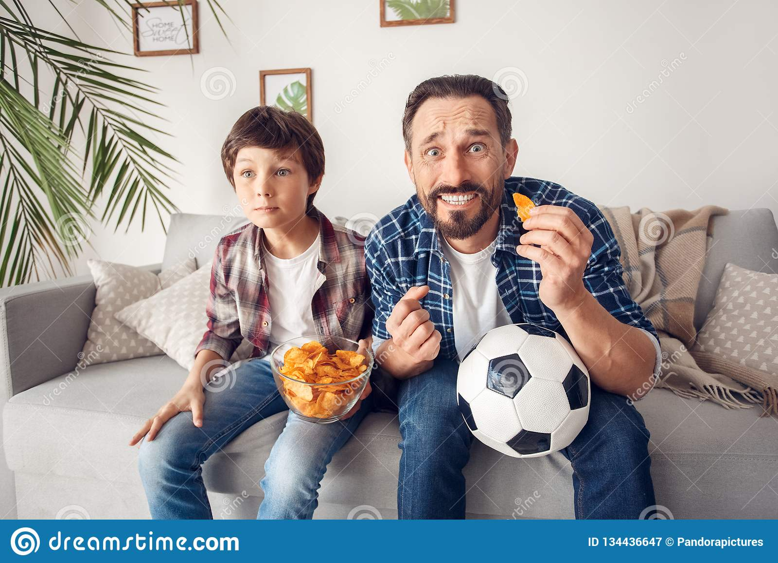Ojciec i mały syn siedzi na kanapy łasowania układu scalonego mienia dopatrywania balowej piłce nożnej nerwowej w domu