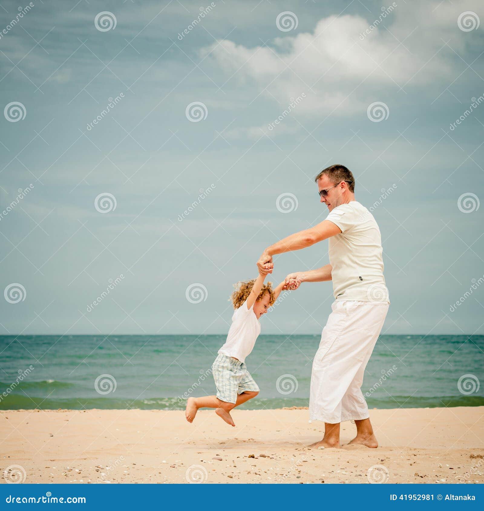 Ojciec i syn bawić się przy plażą