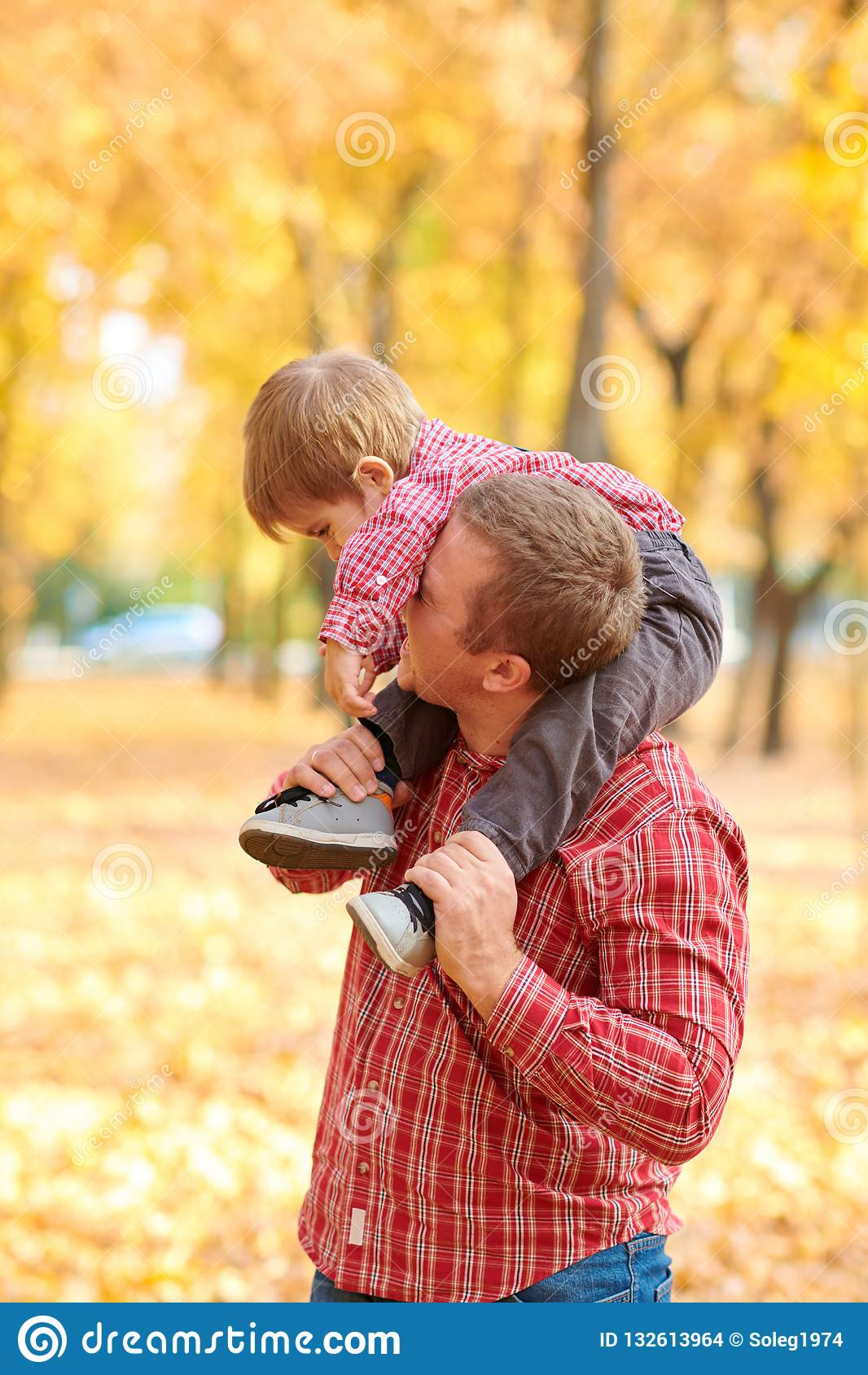 Ojciec i syn bawić się zabawę i mamy w jesieni miasta parku One pozuje, ono uśmiecha się, bawić się Jaskrawi żółci drzewa