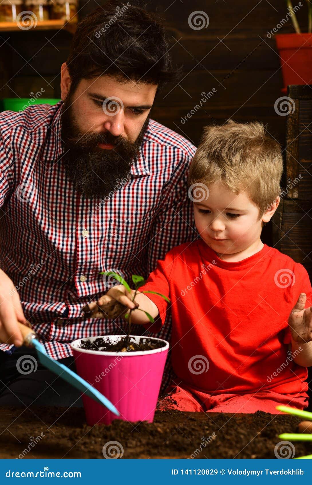 Ojciec i syn Ojca dzień Rodzinny dzień charcica Kwiat opieki podlewanie Glebowi użyźniacze szczęśliwe ogrodniczki z wiosną