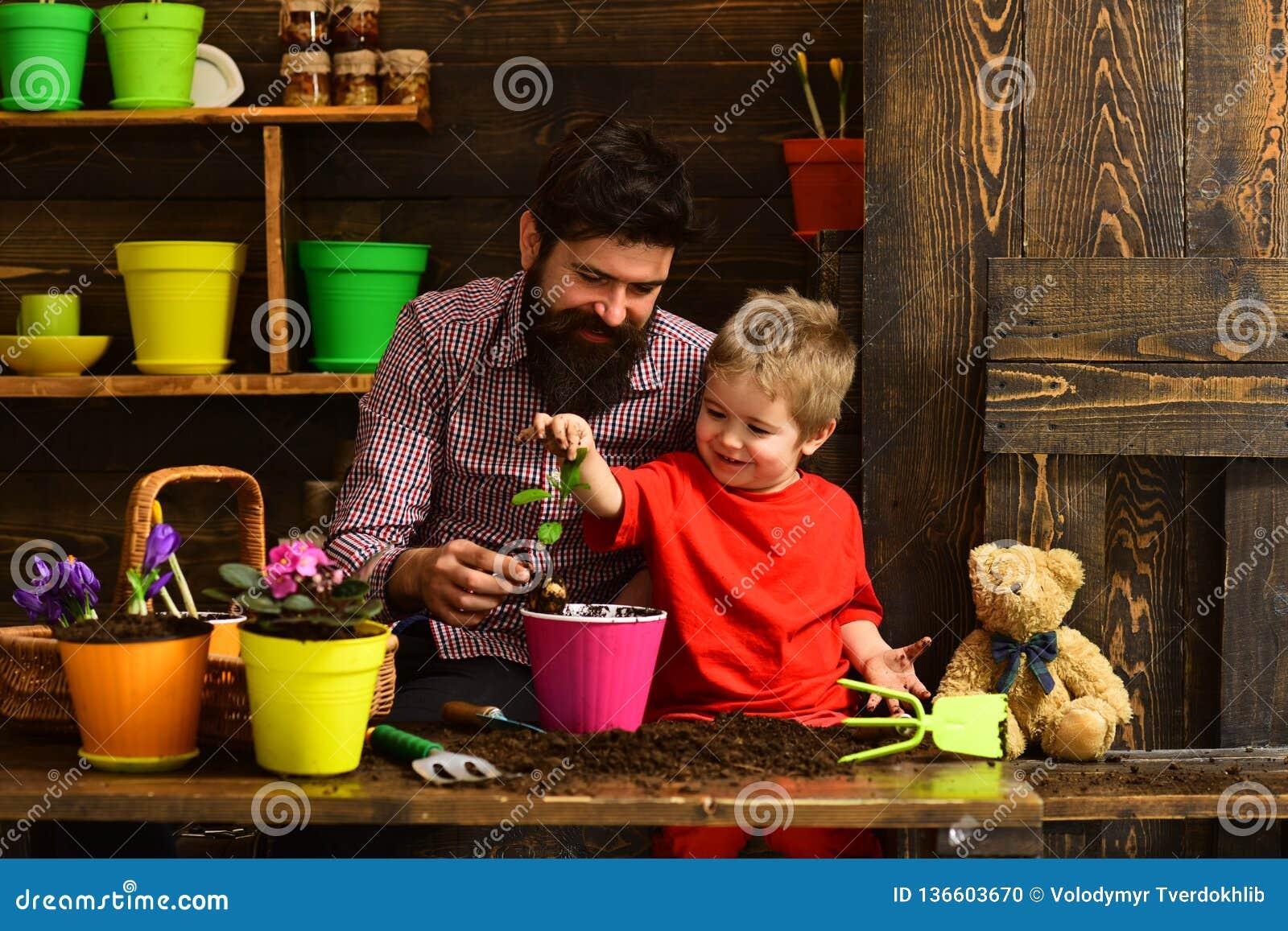Ojciec i syn Rodzinny dzień charcica Brodata mężczyzny i chłopiec dziecka miłości natura szczęśliwe ogrodniczki z wiosną