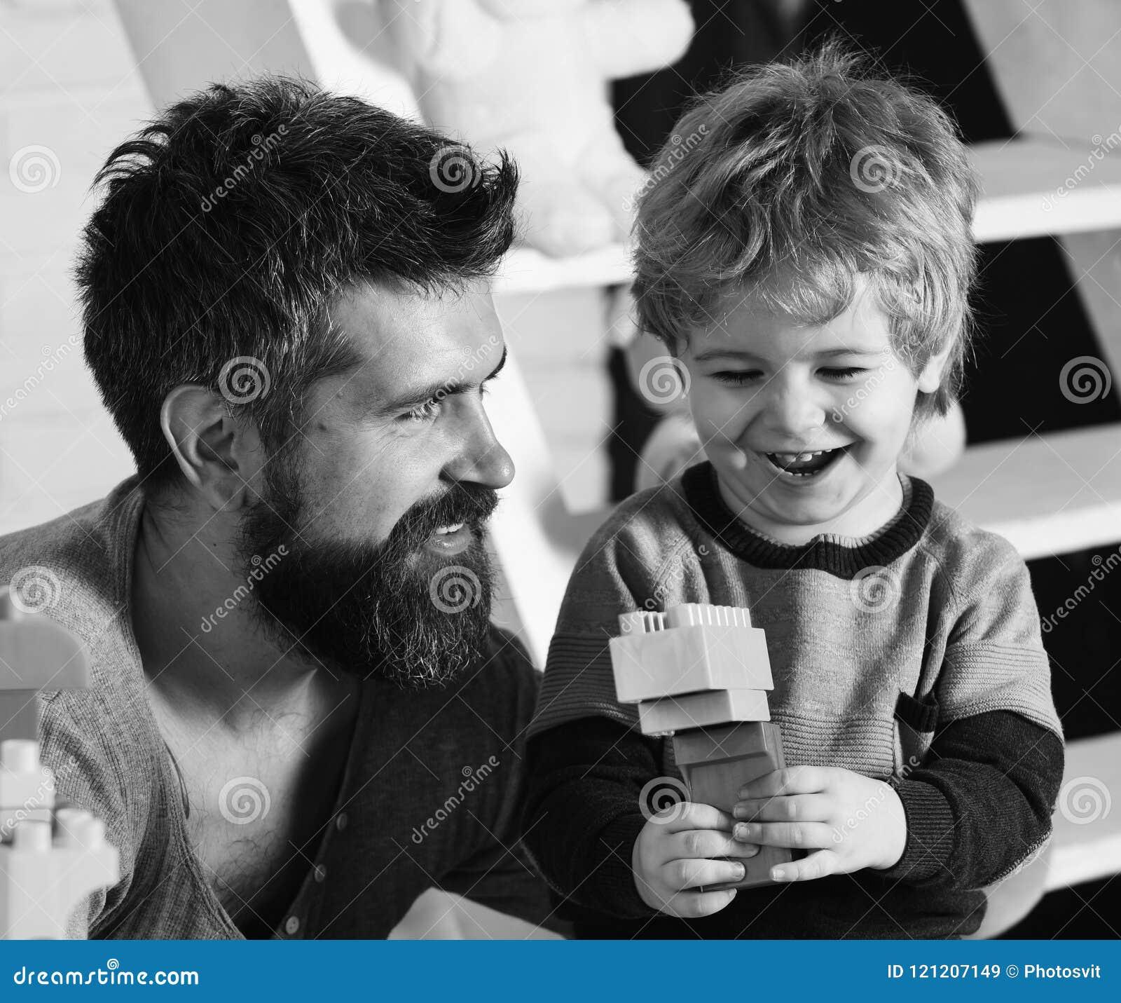 Ojciec i syn z szczęśliwymi twarzami tworzymy kolorowe budowy