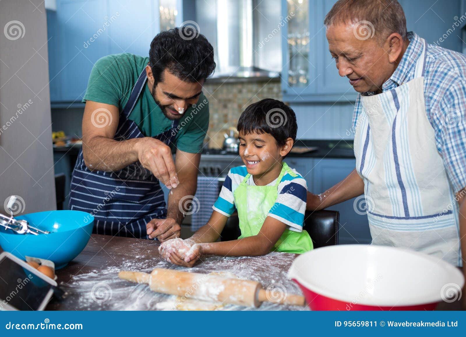 Ojciec tryskaczowa mąka na syn ręce podczas gdy przygotowywający jedzenie z dziadem