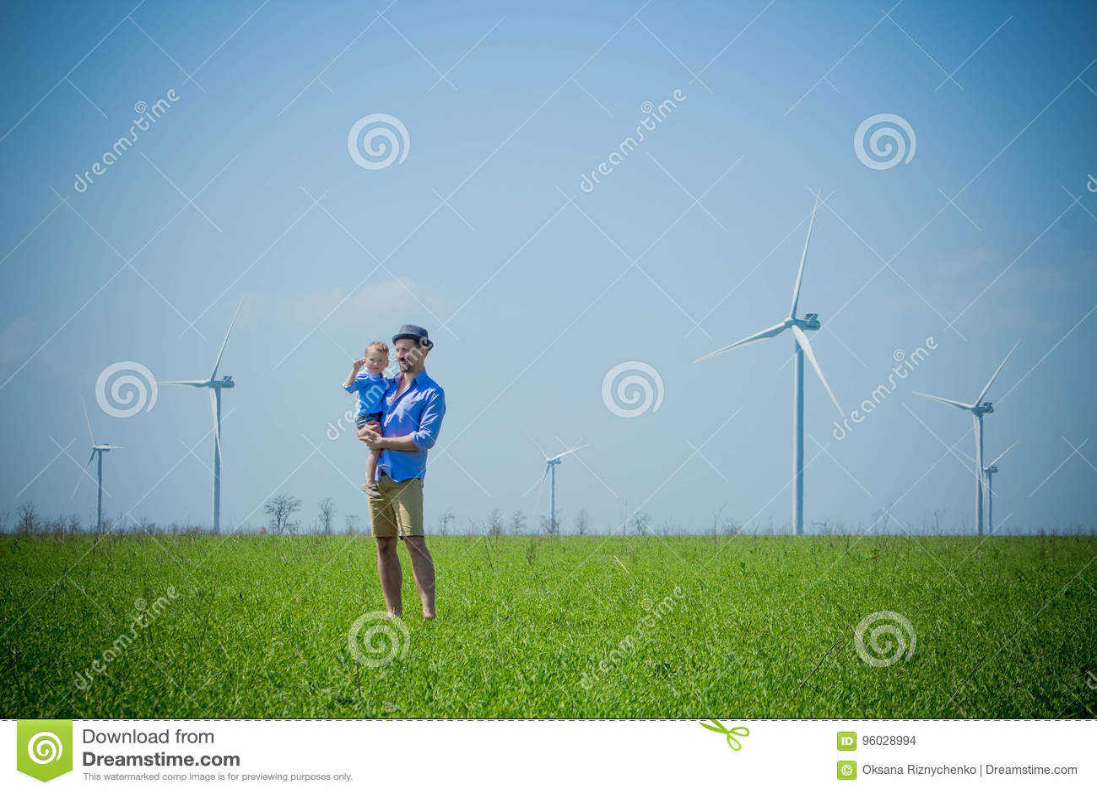 Ojciec trzyma jego syna w jego rękach na życzliwym zieleni polu
