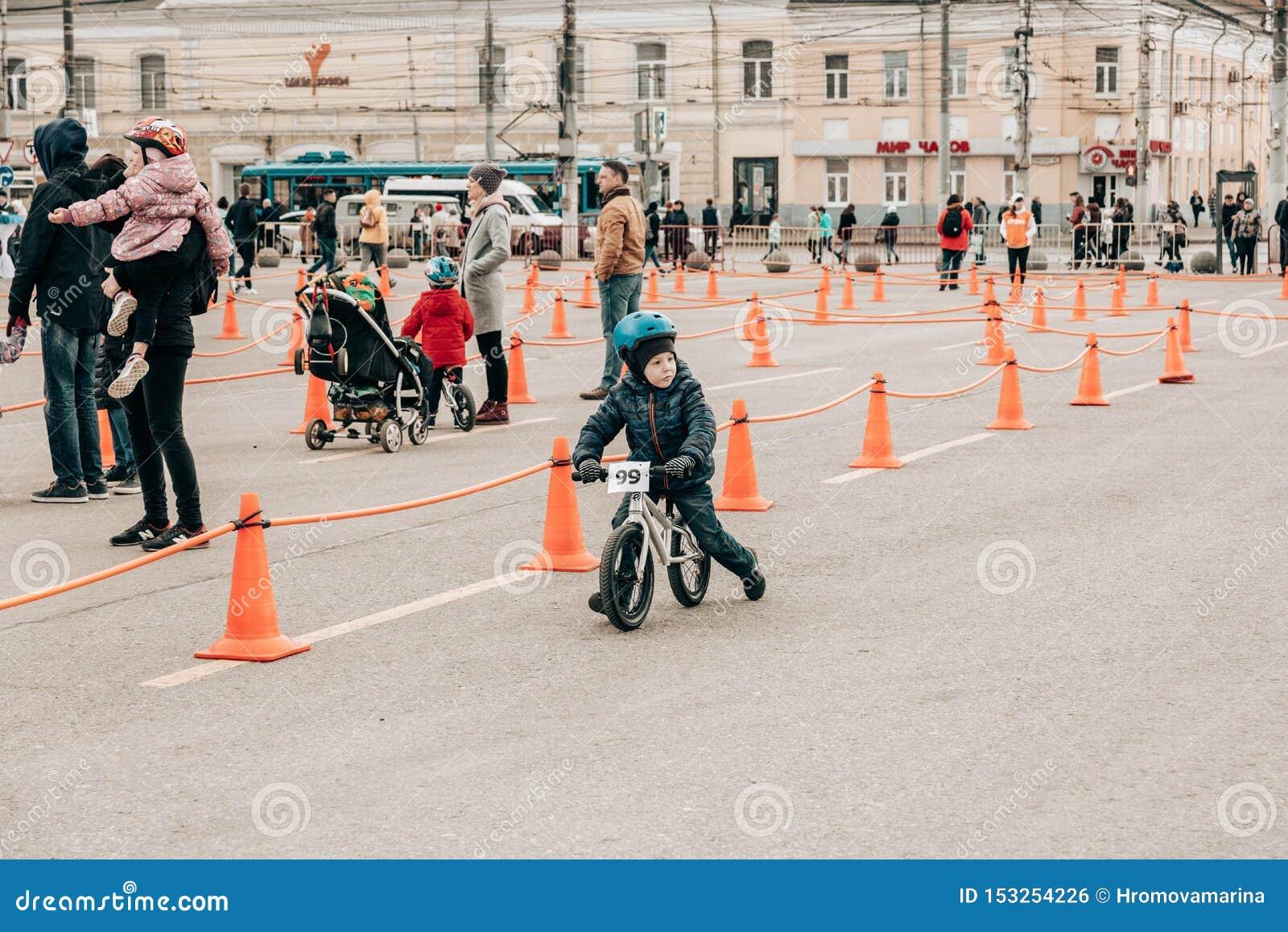 Ojciec trzyma uśmiechniętego dziecka w jego armslittle chłopiec w ochronnym hełmie na amatorskiej rywalizacji balansować bicykl n