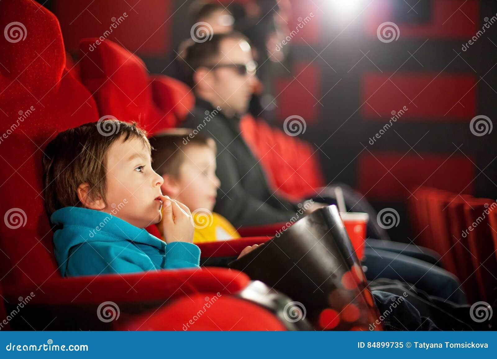 Ojcuje i dwa dziecka, chłopiec, ogląda kreskówka film w cin