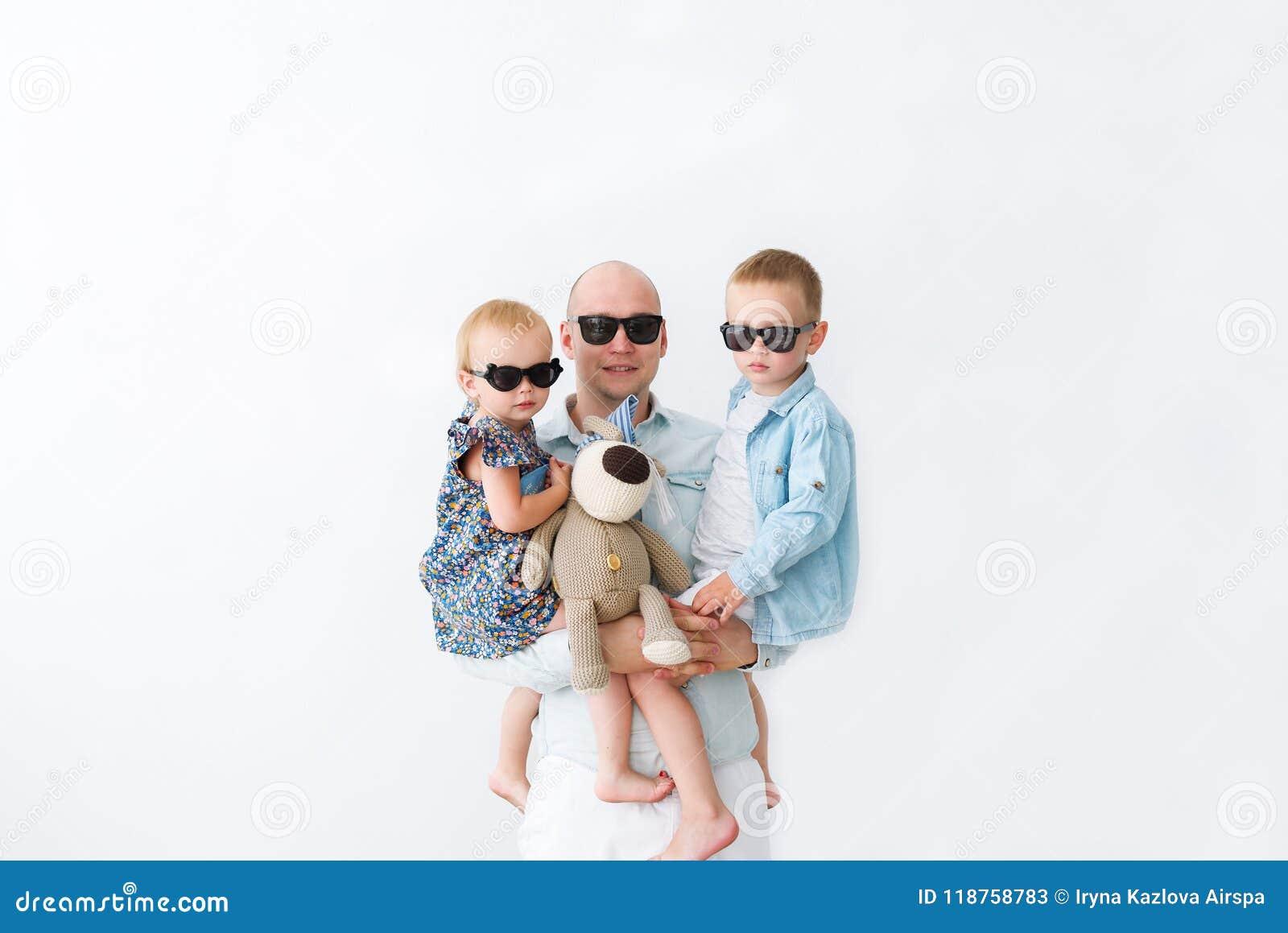 Ojcuje z jego dwa dziećmi patrzeje kamerę w czarnych szkłach Na biel