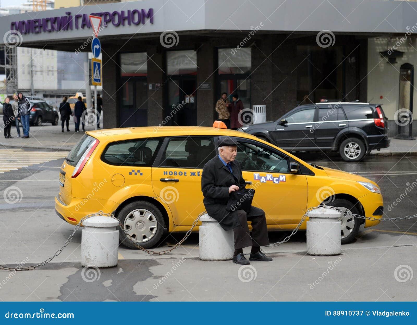 Okänd äldre manantipersonal som vilar på en konkret sockel nära vägen