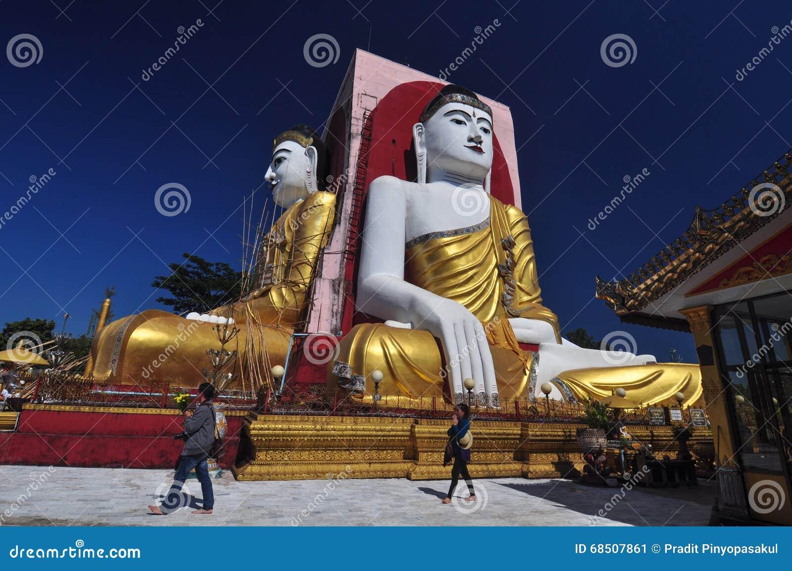 Okända turister ber på Kyaik Pun Pagoda, Myanmar