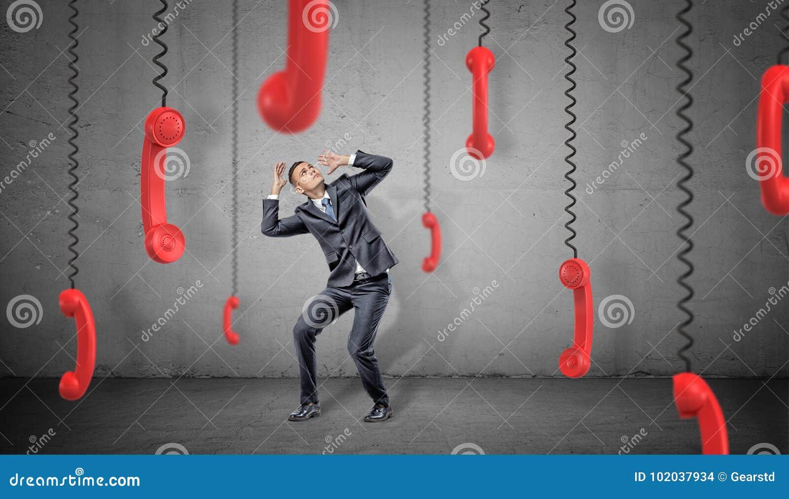 Okaleczający biznesmen na betonowym tle chuje od wiele czerwonych retro telefonów odbiorców wiesza w dół na ich sznurach