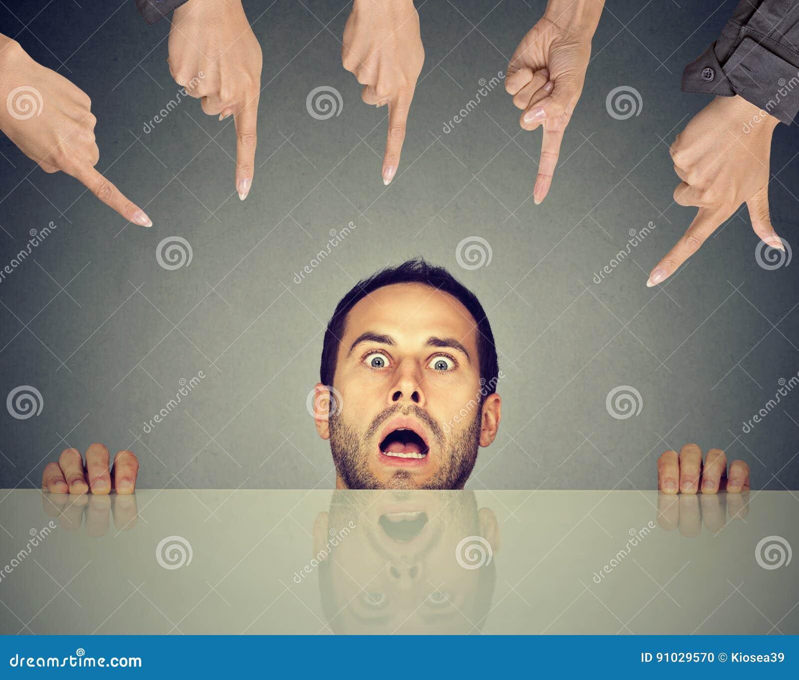 Okaleczający mężczyzna pracownik chuje pod stołem oskarża ludźmi które wskazują palce przy on
