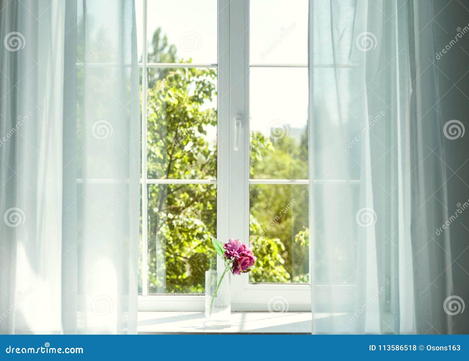 Okno z zasłonami i kwiatami