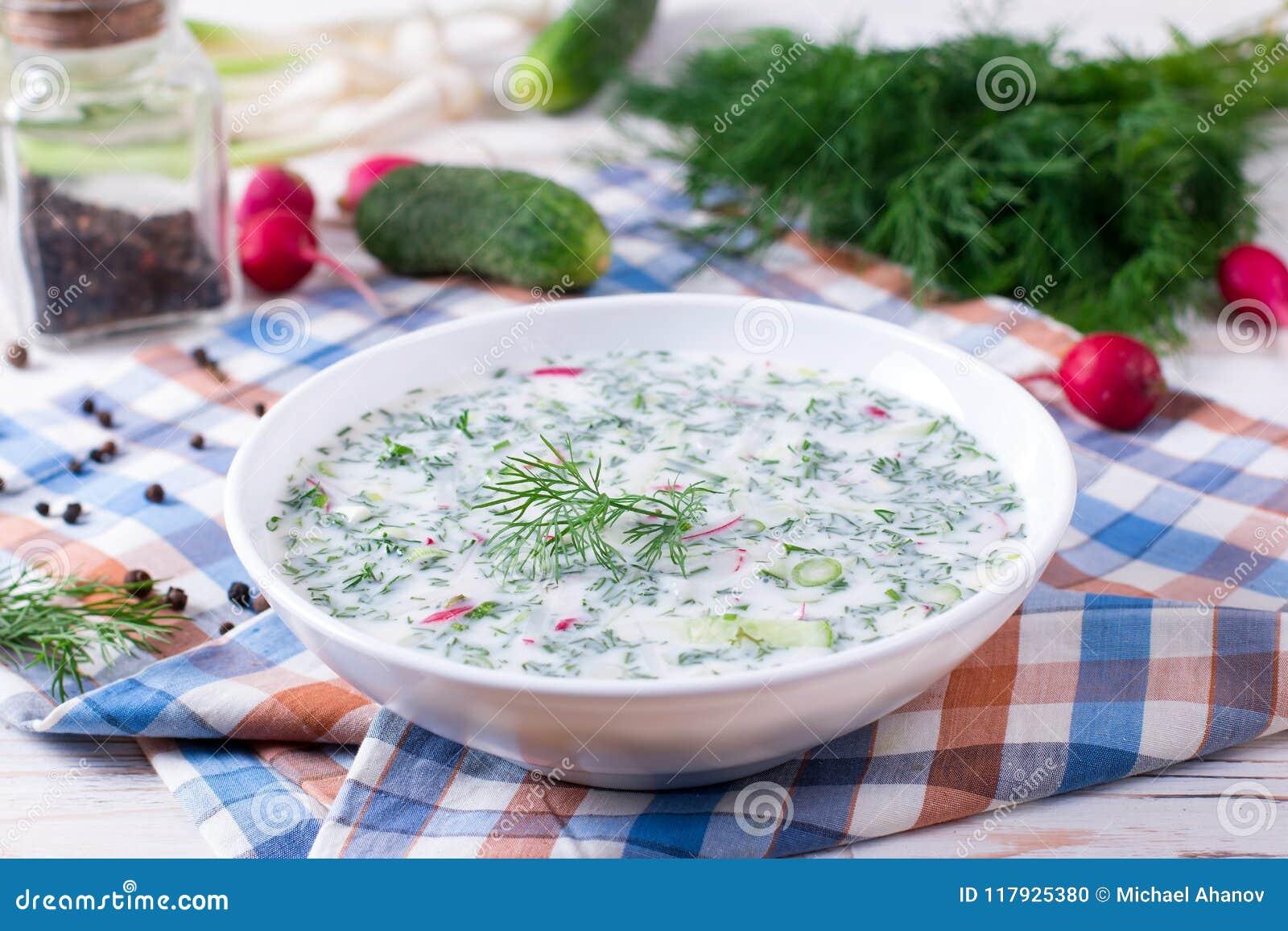 Okroshka. Summer light cold yogurt soup with cucumber, radish, eggs and dill on a table.